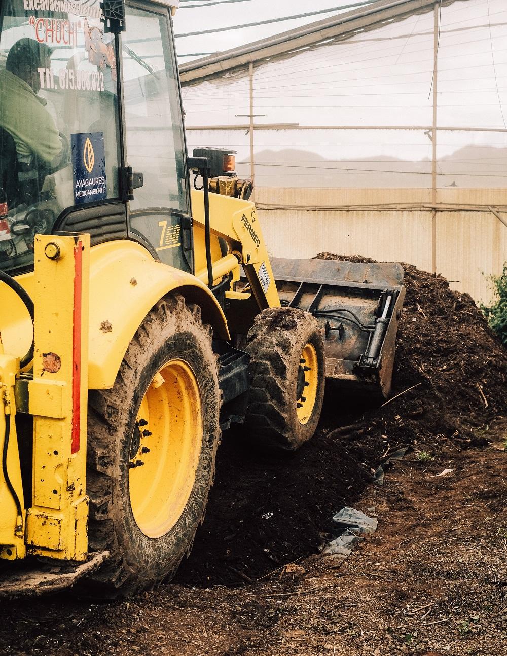 operario municipal conduce máquina manipulando compost