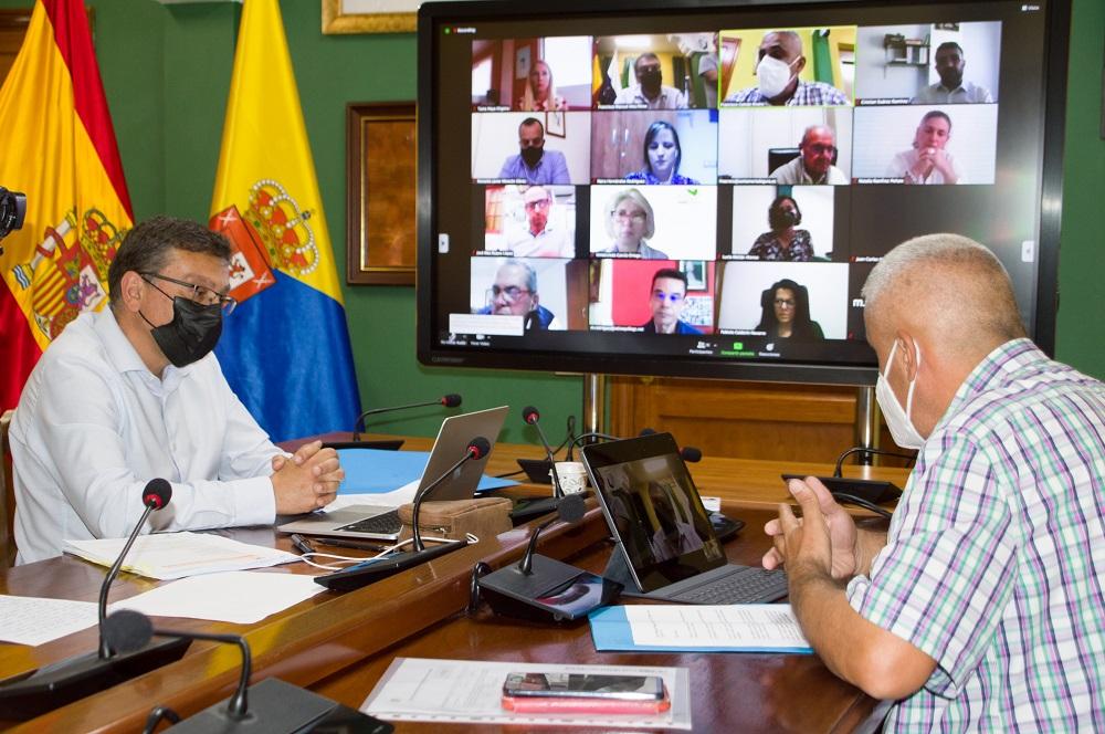 Momento de la sesión plenaria se ve al Alcalde, PAco Gaval y en la pantalla grande al resto de asistentes.