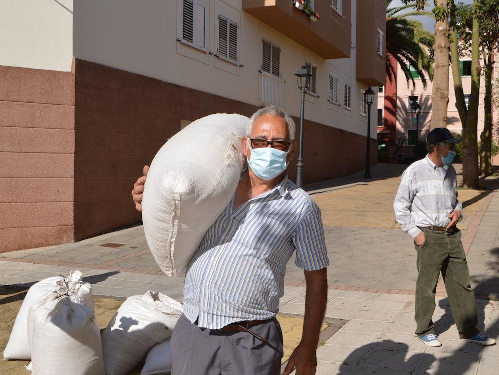 Agricultor carga con saco de semillas