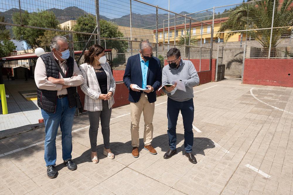 Alcalde y consejero observan documentación en la cancha deportiva mientras concejal y directora del colegio observan