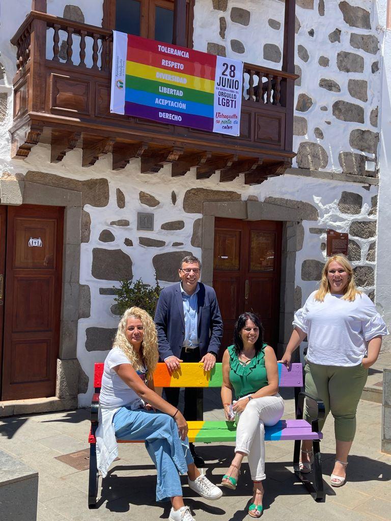 Alcalde y concejala posan junto a representantes en banco arcoiris